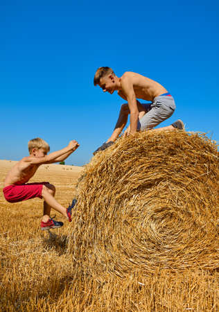 Teenagers in shorts and with open torso jump on haystacks. Wheat hay on agricultural field. Two brothers are fooling around and laughing. Children's day in nature. Rural children on stubble. Friends having fun outdoors. 版權商用圖片