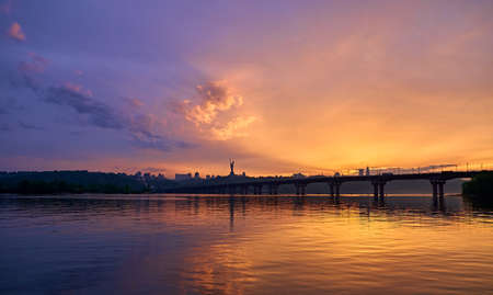 Orange blue sunset on the Dnieper river in Kyiv. Panorama of the bridge. Clouds in the sky.