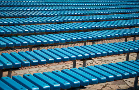 Pattern of blue plastic benches. Striped benches in daylight. Concert venues in front of the crowd.