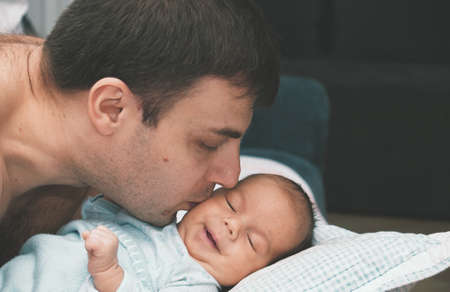 A caring father holds and kisses the baby. Happy family at home. Stock fotó
