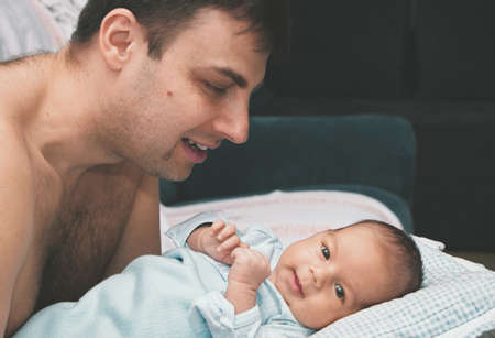 A caring father looks at the baby and smiles at him. Happy family at home.