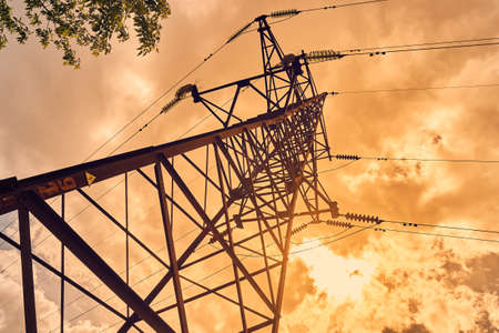 High voltage electric pole and transmission lines. Electricity pylons at sunset and clouds. Power and energy. Energy conservation. High voltage grid tower with wire cable at distribution station.