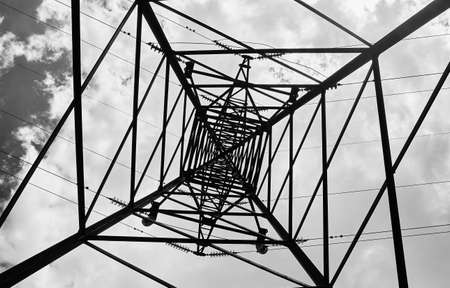High voltage electric pole and transmission lines. Electricity pylons at sunset and clouds. Power and energy. Energy conservation. High voltage grid tower with wire cable at distribution station. Bottom view, black and white.