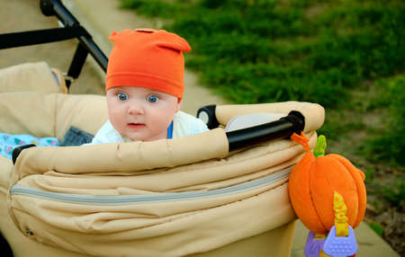 Portrait of a cute infant with a pumpkin and an orange hat. A kid with a surprised look. Baby in a stroller. Tiny with big eyes.