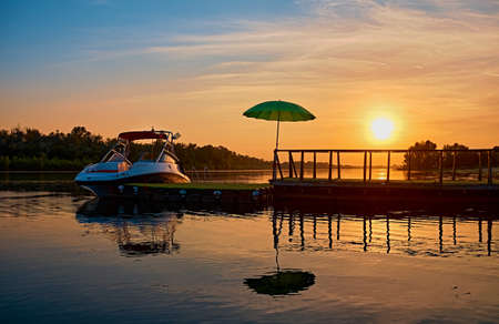 Summer vacation on the water. The yacht is moored to the pier with a green umbrella. Morning sunrise on the river. Beach scene. Mirror reflection of the pontoon.