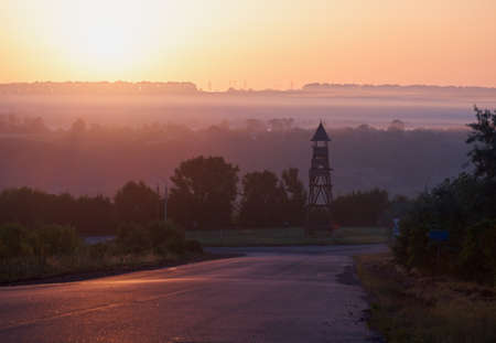 Foggy morning at sunrise. Bluish fog in the sun. Ancient wooden tower in the middle of the road ring. Asphalt road in the fog. Electric poles on the horizon.