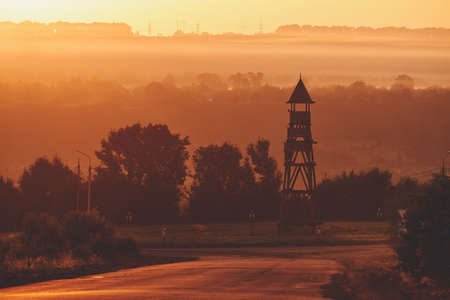 Foggy evening at sunset. Bluish fog in the sun. Ancient wooden tower in the middle of the road ring. Asphalt road in the fog. Electric poles on the horizon. Stock Photo