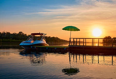 Summer vacation in nature. A small yacht is moored to the pier with a green umbrella after relaxing on the river. Evening sunset on the water. Silhouette of a pontoon with a boat. Beach scene. Mirror reflection.