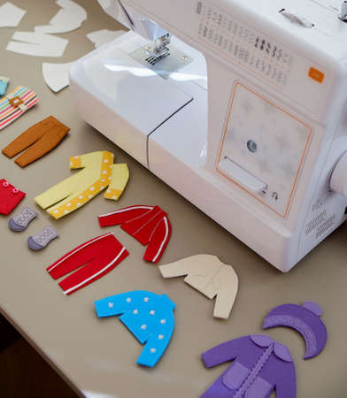 Multi-colored toy felt clothes for dolls on a table near the sewing machine 写真素材