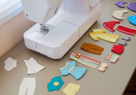 Multi-colored toy felt clothes for dolls on a table near the sewing machine