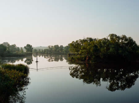 Dawn on the river. A fisherman is standing on the suspension bridge. Vegetation is reflected in calm water.