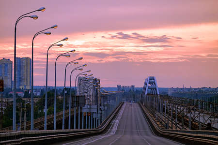 Sunrise across the bridge. View of the skyscrapers of the city. The column of street lamps is illuminated by sunlight.