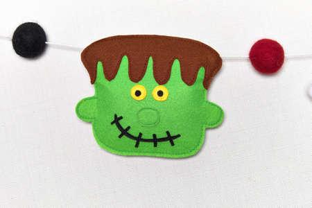 Felt garland for Halloween. Wool balls and symbols. Frankenstein, pumpkin, ghost, vampire and voodoo doll. Handmade fabric.