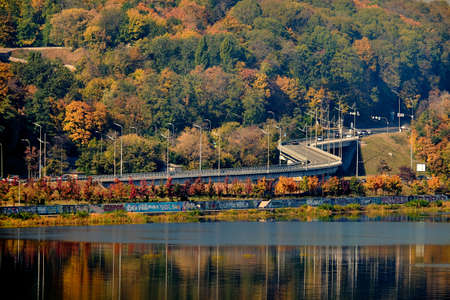 The car overpass crosses lush deciduous trees. Autumn forest by the river. Lampposts are reflected in the water.