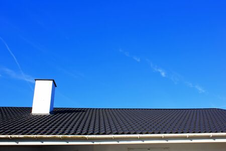 Gray roof and chimney with blue sky. Skylight