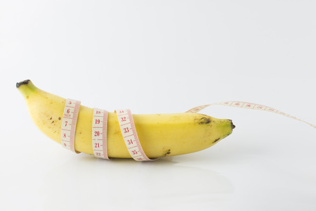 Yellow banana, with measuring tape indicate males penis length, or mens health. It also indicate food for fitness & diet.
