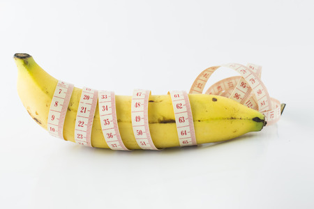 Yellow banana, with measuring tape indicate male's penis length, or men's health. It also indicate food for fitness & diet.