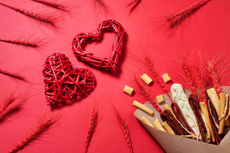 Original edible gift for man in the form of a bouquet consisting of sausages, smoked cheese, spicy cheese, red stalks of rye wrapped in craft paper on the red background with two red hearts woven from twigs, top view.