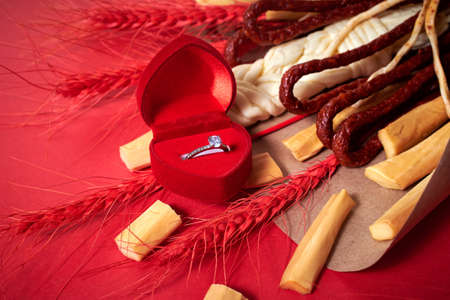 Original edible gift in the form of a bouquet consisting of sausages, smoked cheese, spicy cheese, red stalks of rye wrapped in craft paper on the red background, top view, copy space. Extraordinary marriage proposal and engagement concept. For Valentine's day, wedding cutlery, romantic dinner, declaration of love, love confession, date. Red velvet ring box, engagement brilliant ring.