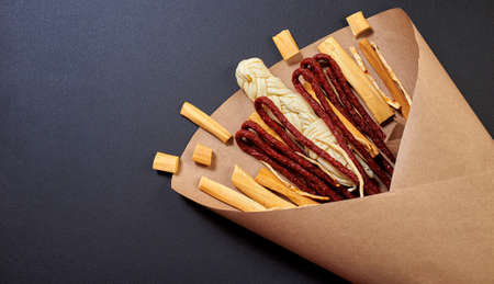 Original edible bouquet consisting of sausages, smoked cheese, spicy cheese, wrapped in craft paper on the black background, top view, copy space.