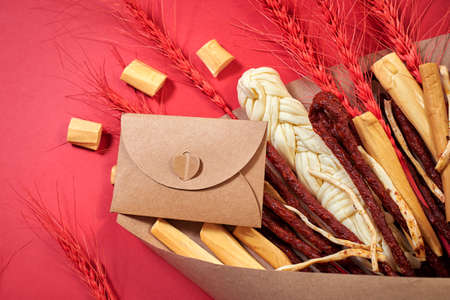 Extraordinary declaration of love. Original edible gift in the form of a bouquet consisting of sausages, smoked cheese, spicy cheese, red stalks of rye wrapped in craft paper on the red background, top view, copy space. Love message in a craft paper envelope. For Valentine's day, wedding cutlery, romantic dinner, declaration of love, love confession, date.