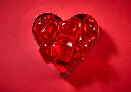 the heart is made up of candy in the shape of hearts on a red background.