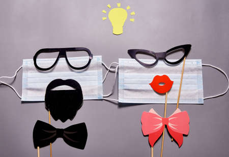 Two medical masks with glasses, lips and mustaches with a yellow paper light bulb above them on a gray background