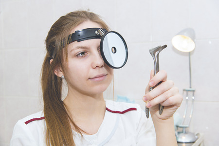Female medicine doctor examining patient with nasal mirror. Otorhinolaryngologist or ENT examination. Stock Photo