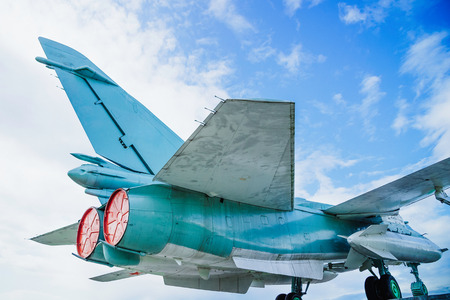 Russian jet combat aircraft tail side with red engine plugs under blue sky