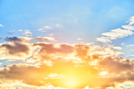 Clouds on the clear blue sky and sun with lens flare