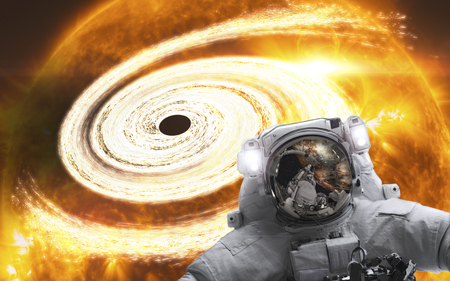 Astronaut in the space with orange giant  black hole behind. Science fiction. Trouble in the space.