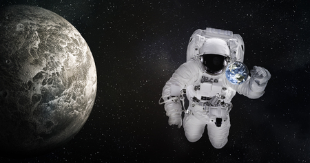 Single giant astronaut in outer space near tiny Earth planet and moonlike planet of solar system with reflection in helmet. Science fiction