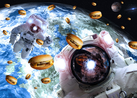 Astronauts in outer space with cheseburgers on the Earth and Marts planets on the background