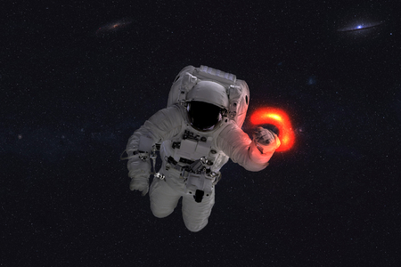Space astronaut near black hole red glow. Space adventure in outer space. Science fiction.
