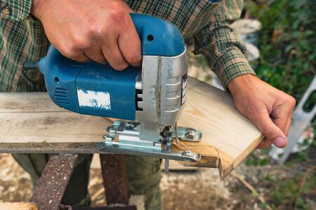 Electric jigsaw in the hands sawing wooden Board on the workbench outside