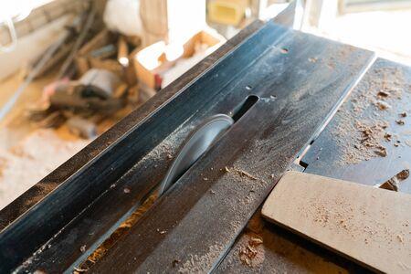 Working woodworking machine with circular saw. Selective focus. Manual wood processing concept.