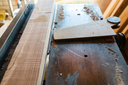 Working woodworking machine with cutting board on it closeup. Selective focus. Manual wood processing concept.