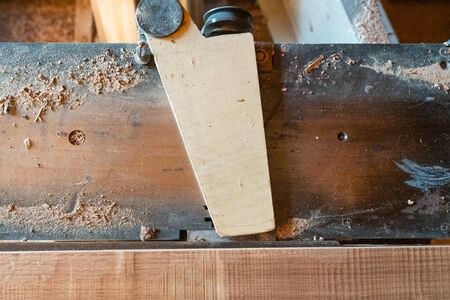 Working woodworking machine with secure covered plane with sawdust close up. Selective focus. Manual wood processing concept. Zdjęcie Seryjne