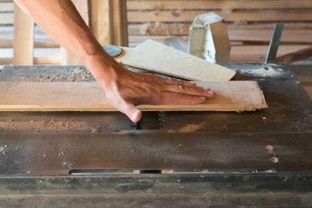 Woodworking machine plane process a wooden plank. Workers hand hold a wooden plank. Manual wood processing concept.