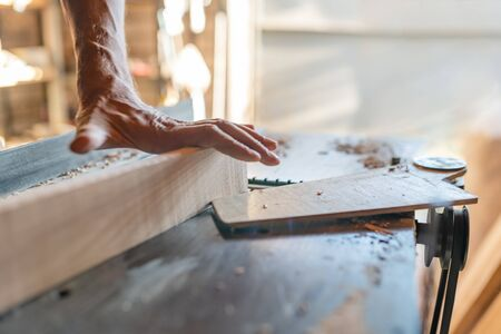 Woodworking machine process a wooden plank. Workers hand hold a wooden plank. Motion blur. Stok Fotoğraf