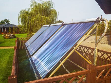 Vacuum collectors on the backyard. Solar panels for water heating with lens flare. Stockfoto