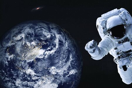 Astronaut near night Earth planet of solar system Closeup. Outer journy. Science fiction. Elements of the image were furnished by