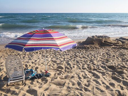Sun lounger and umbrella on the beach by the sea under a blue cloudless sky 版權商用圖片