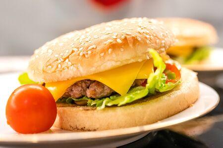 Homemade hamburger with cherry tomato on the plate closeup. Selective focus Фото со стока - 134853314