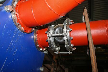 Anti-vibration rubber expansion joint in the pipeline in industrial production line. Red and blue pipes Selective focus.