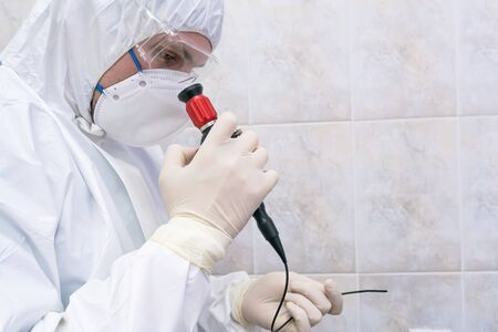 Doctor in protective suit with short fiber endoscope at pandemic period. Epidemic disease concept. Selective focus.