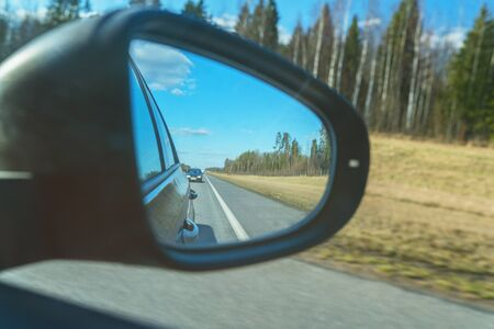 Dark road reflection with asphalt lines on side mirror rear view of moving car Suitable for any purpose use