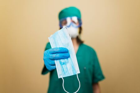 Woman doctor in green suit holds medical mask in had with blue glove on the yellow background. Medical concept. Selective focus.