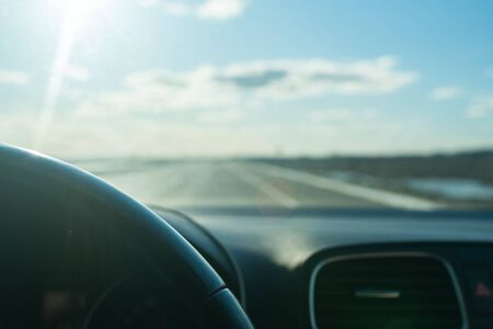 View from inside the moving car on the road, Blue sky. transportation concept. Lels flare. Selective focus.