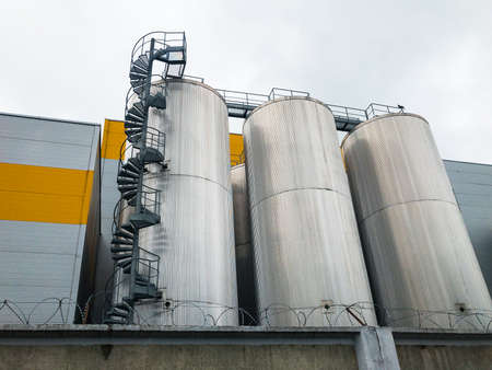 Big metal insulated storage containers with a spiral staircase and bridge. Designed for storing substances at constant temperatures.